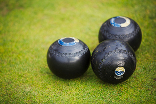Three round wooden black lawn bowls on a smooth playing surface.の写真素材 [FYI02261334]