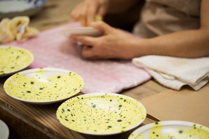 Close up of person working in a Japanese porcelain workshop, applying yellow glaze to white plates.の写真素材 [FYI02261357]