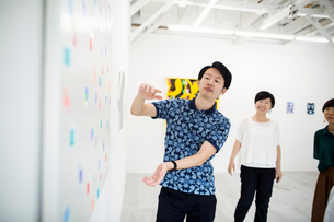 Man wearing blue shirt standing next to modern painting on white wall in art gallery, two women stanの写真素材 [FYI02261368]