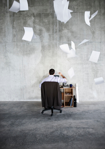 Caucasian businessman throwing papers in air while sitting at his desk in a large raw space.の写真素材 [FYI02261369]