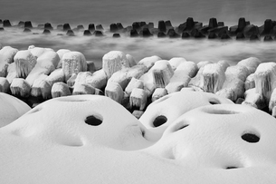Snow-covered wave breakers on a rocky beach in winter.の写真素材 [FYI02261373]