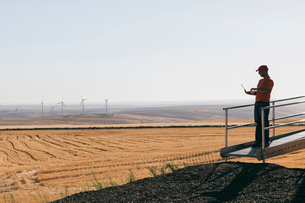 A wind farm technician standing and using a laptop at the base of a turbine on a wind farm in open cの写真素材 [FYI02261390]