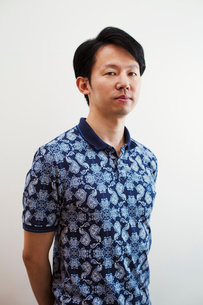 Portrait of man with short black hair wearing blue patterned shirt standing in art gallery, lookingの写真素材 [FYI02261414]