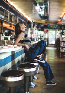 Side view of woman wearing jeans and sleeveless top leaning against a bar counter in a restaurant, lの写真素材 [FYI02261423]