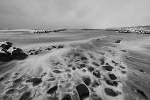 Snow-covered wave breakers on a rocky beach in winter.の写真素材 [FYI02261424]