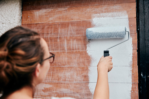 A woman using a paint roller, painting wooden planks on a wall.の写真素材 [FYI02261434]