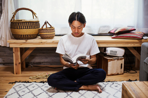 Man sitting indoors on a rug, leaning against wooden bench with baskets, crossed legs, reading.の写真素材 [FYI02261441]