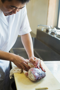 Chef working at a counter at a Japanese sushi restaurant, gutting and cleaning whole fresh sea breamの写真素材 [FYI02261460]