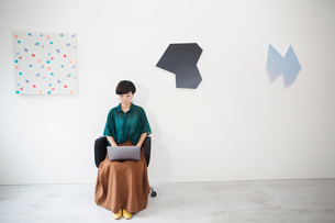 Woman with short black hair wearing green shirt sitting in art gallery, typing on laptop computer.の写真素材 [FYI02261461]