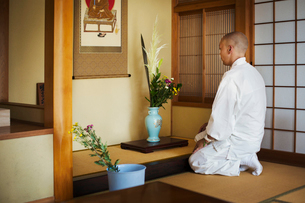 Side view of Buddhist monk with shaved head wearing white robe kneeling in front of vase with flowerの写真素材 [FYI02261462]