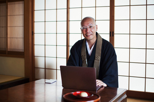 Buddhist monk with shaved head wearing black robe sitting indoors at a table, using laptop computer,の写真素材 [FYI02261463]