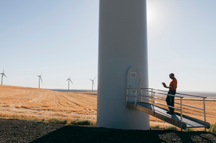 A wind farm technician standing and using a laptop at the base of a turbine on a wind farm in open cの写真素材 [FYI02261464]