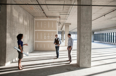 Mixed race team of business people touring a new empty raw office space.の写真素材 [FYI02261467]