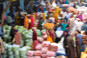 High angle view of fruit and vegetable market, woman carrying a load on her head, motion blur.の写真素材 [FYI02261479]