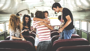 A group of young people in a party on a school bus.の写真素材 [FYI02261497]
