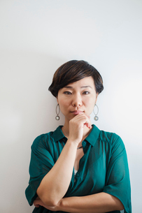 Woman with short black hair wearing green shirt standing in art gallery, hand on chin, looking at caの写真素材 [FYI02261513]