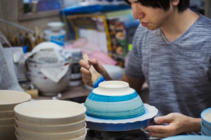 Close up of man working in a Japanese porcelain workshop, painting white bowls with blue glaze.の写真素材 [FYI02261514]