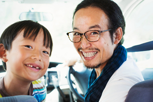 Man wearing glasses and boy sitting in a car, smiling at camera.の写真素材 [FYI02261520]