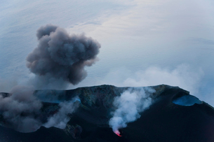 Plumes of smoke and lava emanating from a volcano.の写真素材 [FYI02261521]