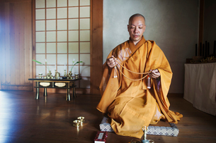 Buddhist monk with shaved head wearing golden robe kneeling indoors in a temple, holding mala.の写真素材 [FYI02261522]