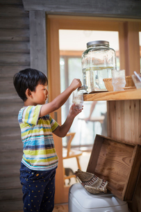 Boy with black hair wearing stripy T-shirt filling drinking glass with water from water dispenser.の写真素材 [FYI02261526]