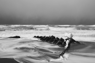 Snow-covered wave breakers on a rocky beach in winter.の写真素材 [FYI02261530]