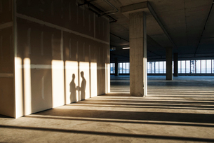 Shadows of business people cast on the sheet rock wall of a large empty raw office space.の写真素材 [FYI02261531]