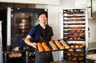 Man working in a bakery, holding large tray with freshly baked rolls, smiling at camera.の写真素材 [FYI02261533]