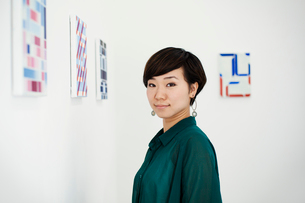 Woman with short black hair wearing green shirt standing in art gallery, looking at camera.の写真素材 [FYI02261534]
