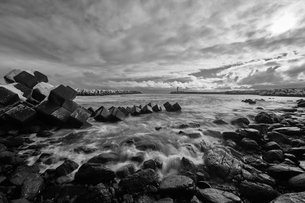 Snow-covered wave breakers on a rocky beach in winter.の写真素材 [FYI02261537]