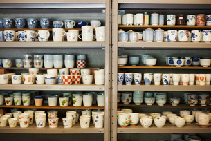 Large selection of ceramic cups and mugs on shelves in a Japanese porcelain workshop.の写真素材 [FYI02261540]