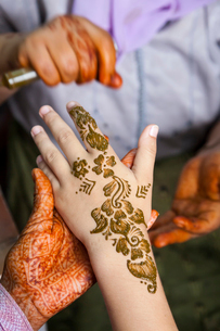 High angle close up of henna tattoos being put on hand.の写真素材 [FYI02261544]