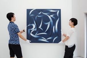 Man in blue shirt and woman wearing white shirt hanging modern painting on white wall in art galleryの写真素材 [FYI02261547]