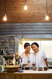 Man and woman standing in a kitchen, cleaning dishes, smiling.の写真素材 [FYI02261568]