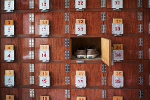 A row of shoe lockers with one open door, and one pair of shoes stored.の写真素材 [FYI02261574]