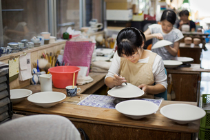 Women sitting in a workshop, working on Japanese porcelain bowls.の写真素材 [FYI02261575]