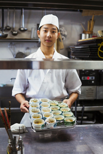 Chef working in the kitchen of a Japanese sushi restaurant, holding tray with small bowls of food.の写真素材 [FYI02261583]