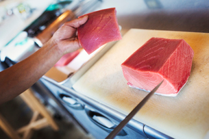 High angle close up of chef working at a counter at a Japanese sushi restaurant, slicing fillet of tの写真素材 [FYI02261590]