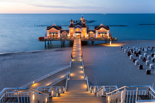 Wooden stairway and walkway leading across sandy beach towards illuminated building on a pier.の写真素材 [FYI02261603]