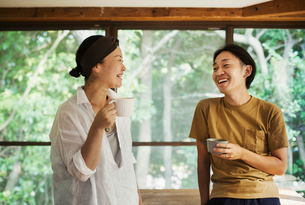 Man and woman standing indoors, holding coffee mugs, lookign at each other, smiling.の写真素材 [FYI02261608]