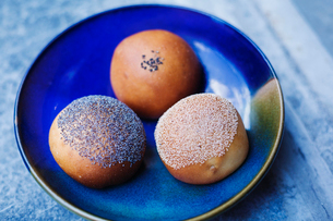 High angle close up of three freshly baked rolls on a blue plate.の写真素材 [FYI02261611]