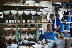Man standing in a Japanese porcelain workshop with shelves of various porcelain bowls.の写真素材 [FYI02261614]