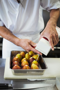 High angle close up of chef working in the kitchen of a Japanese sushi restaurant, preparing figs inの写真素材 [FYI02261618]