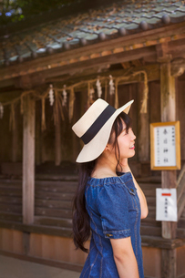 Young woman wearing blue dress and hat standing at Shinto Sakurai Shrine, Fukuoka, Japan.の写真素材 [FYI02261626]