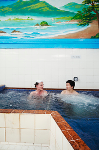 A young Caucasian man and Japanese man seated in a deep pool of moving water in a public bath house.の写真素材 [FYI02261627]