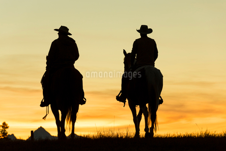 Two cowboys riding on horseback in a Prairie landscape at sunset.の写真素材 [FYI02261635]