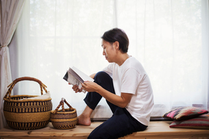 Man sitting indoors on a wooden bench with baskets, crossed legs, reading.の写真素材 [FYI02261637]