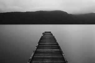 Wooden pier stretching out into the water at Towada Lake with mountains in the distance.の写真素材 [FYI02261653]