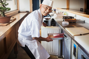 Chef working at a counter at a Japanese sushi restaurant, putting metal tray with fish in refrigeratの写真素材 [FYI02261658]