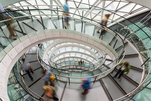 Interior view of building with people walking along glass and metal spiral staircase.の写真素材 [FYI02261663]
